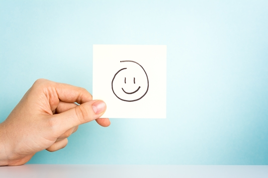 Happy employee. Hand holding a illustration of a happy emoticon or icon on blue background.